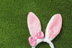 Funny headband with Easter bunny ears on green grass, top view. Space for text stock photo