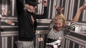 Funny hip hop man dancing with cheerful girl under falling money banknotes. Funny hip hop caucasian man in sport jacket and spiked cap dancing with cheerful stock video