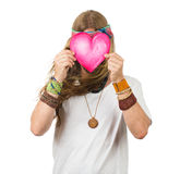 Funny hippie holding a love heart over his face. Funny portrait of a hippie man with a love heart over his face. Isolated on white stock photo