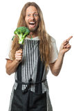 Funny hippie man holding broccoli on a fork. Silly hippie holding a broccoli head on a fork pointing at copy-space. Isolated on white Stock Photos