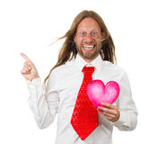 Funny hippie man holding a love heart and pointing. Portrait of a silly and funny hippie man holding a love heart pointing at copyspace. Isolated on white stock image