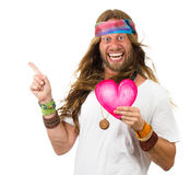 Funny hippie man holding a love heart and pointing. Funny, smiling hippie man holding a love heart and pointing up at copy-space. Isolated on white royalty free stock image