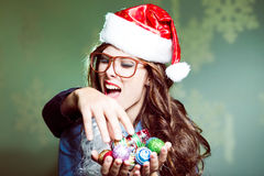 Funny hipster girl in glasses biting intruders. Funny hipster girl in glasses biting intruder's hand and saving Christmas tree decorations wearing xmas santa hat Royalty Free Stock Photos