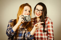 Funny hipster girls taking pictures with an old camera Royalty Free Stock Images