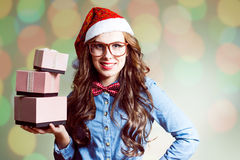 Funny hipster in santa hat holding three boxes of Royalty Free Stock Images