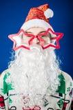 Funny hipster young man wearing Santa Claus beard Stock Photos
