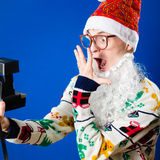 Funny hipster young man wearing Santa Clous beard Stock Photos