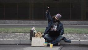 Funny homeless beggar winning a fortune online. Funny homeless beggar using a laptop while receiving a good news as a surprising inheritance or winning a fortune stock video