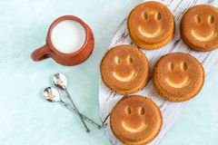 Funny homemade cupcakes in form of smiling face. Funny cupcakes in form of smiling face and mug with milk. Food that causes positive emotions. Humorous sweet Royalty Free Stock Photos