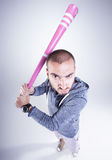 Funny hooligan with a pink baseball bat looking angry in the studio Royalty Free Stock Image