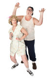 Funny Housewife Dancing in Front of Husband. Wife dancing to music with an annoyed husband stock photo