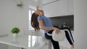 Funny housewife female dancing and sings with plates in arms while cooking meal at kitchen at home stock video footage