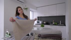 Funny housewife female is ironing fresh towels and fooling around and singing stock footage