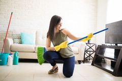 Funny housewife having fun with a broom. Young beautiful woman playing around with a broom and pretending it`s a guitar Stock Image