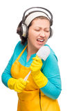 Funny housewife holding a brush instead of a microphone. Isolated Stock Images