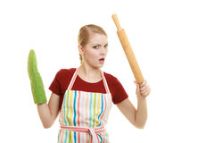 Funny housewife in kitchen apron holds baking rolling pin stock images