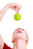 Funny housewife in kitchen apron trying to eat apple timer isolated Royalty Free Stock Images