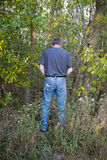 Funny Humor Man Pee in Woods. Nature calls! Funny humor of a man taking a pee in the woods. This male has got to go and needs to urinate in the great outdoors Royalty Free Stock Photography
