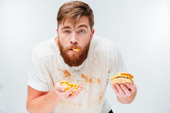 Funny hungry bearded man eating junk food. Isolated on white background Stock Photo