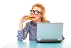Funny hungry business woman eating sandwich. On work, isolatd on white. Studio shot Royalty Free Stock Photo