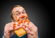 Funny hungry fat man dirty by ketchup. Eating the tasty sandwich Stock Images