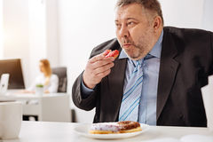 Funny hungry office worker gobbling doughnuts Stock Images