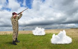 Funny Hunter, Hunting Rain Clouds, Surreal. A surreal funny hunter is hunting and shooting rain clouds in the sky. A dead cloud falls to the ground after being Stock Photo