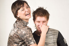 So funny I am. Two young beautiful people joking: girl holding nose of her boyfriend leading him by the nose stock photography