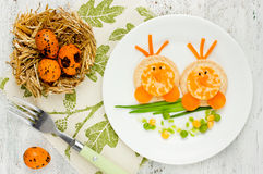 Funny idea for baby healthy shaped chick. Easter breakfast for kids. Funny idea for baby healthy shaped animals food Cute chick from cheese crackers green onion Stock Image
