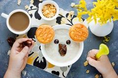 Funny idea for healthy kids breakfast - oat bran porridge bowl i Royalty Free Stock Images