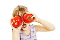 Funny image of little girl showing tomatoes. Royalty Free Stock Photography