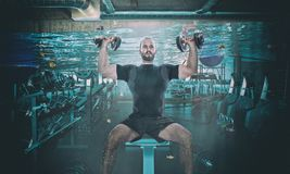 Extreme workout situation. Funny image of man training with dumbbell in a flooaded gym royalty free stock photography