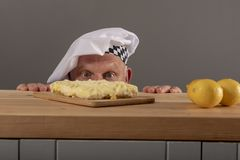 Funny image of a mature chef looking at a lemon cake. He has made stock photography