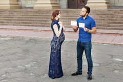 Funny image. Сouple expecting a baby: man holds a signs Royalty Free Stock Photo