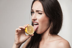 Funny image of young woman eating lemon Stock Images