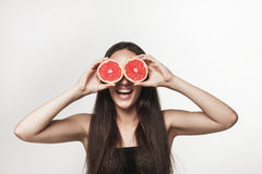 Funny image of young woman holding grapefruit Stock Images