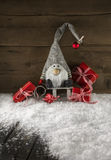Funny imp on wooden background with red christmas presents. Stock Photos