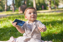 Funny infant baby boy with mobile phone in the summer pak. Stock Images