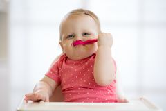 Funny infant baby spoon eats itself. Funny infant baby girl spoon eats itself royalty free stock photo