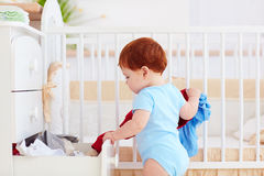 Funny infant baby throwing out clothes from the dresser at home. Cute funny infant baby throwing out clothes from the dresser at home Royalty Free Stock Image