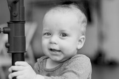 Funny infant boy with a smirk on his face. Cute grinning toddler kid looking at camera. Black and white. Blured background stock photos