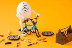 Funny insane egg repairing bicycle. With various tools Stock Photo