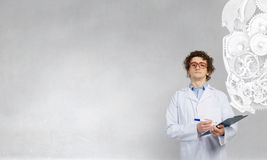 Funny intern doctor . Mixed media. Young doctor in medic coat and glasses with folder in hands Stock Photo