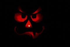 Funny Jack-O-Lantern Face In The Dark. A pumpkin carved into a jack-o-lantern and lit from inside with a candle, photographed outdoors in the dark on Halloween Royalty Free Stock Photography