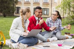 Beautiful girls laughing while their fellow student joking. Funny jokes. Beautiful pleasant girls laughing out loud while their fellow student joking funnily in Royalty Free Stock Image