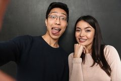 Funny joyful asian couple posing together and making selfie. While showing grimaces and looking at the camera over black background Stock Images