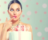 Funny joyful beauty model girl holding big beautiful party or birthday cake. Over green background and tasting it stock photo