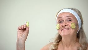 Funny joyful granny with cucumber mask on face smiling on camera, cosmetology royalty free stock image