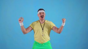 Funny joyful male trainer from the 80`s with a mustache and glasses with a stopwatch slow mo