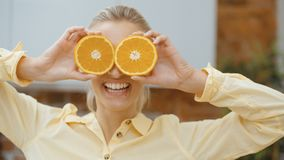 Young woman holding orange slices near her eyes and smiling. stock video footage